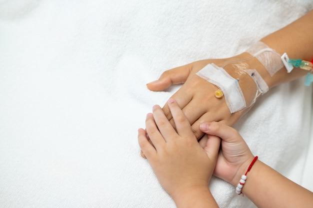 手を携えて、励ましと懸念のために病院で古い患者の手を握っている子供。