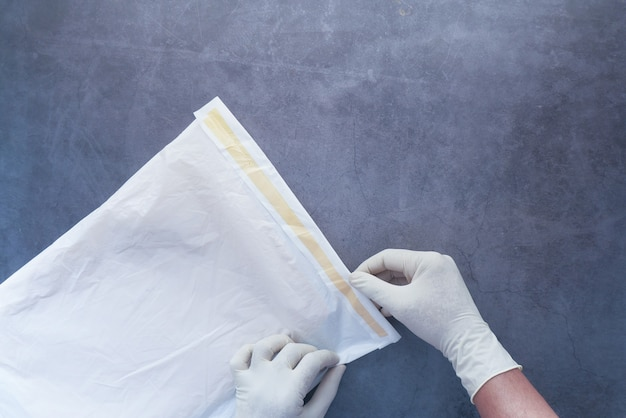 郵便船用の白い紙の泡の封筒を保持しているラテックス手袋を手に