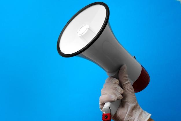 Рука в медицинской перчатке, держащей громкоговоритель на синем фоне