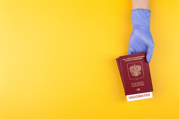 Рука в медицинской перчатке, держащей паспорт с вакциной штампом на желтом фоне