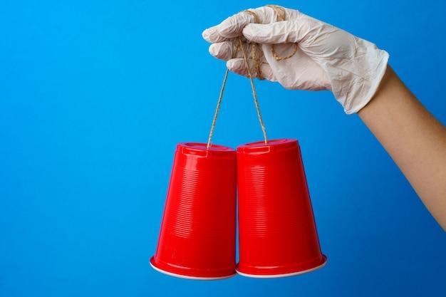 プラスチック製のコップとひもで作られたおもちゃの電話を保持している医療用手袋を手に