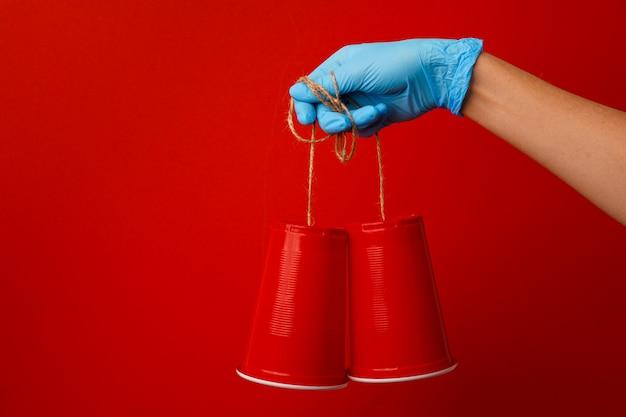 Рука в медицинской перчатке держит игрушечный телефон из пластикового стакана и шнурка