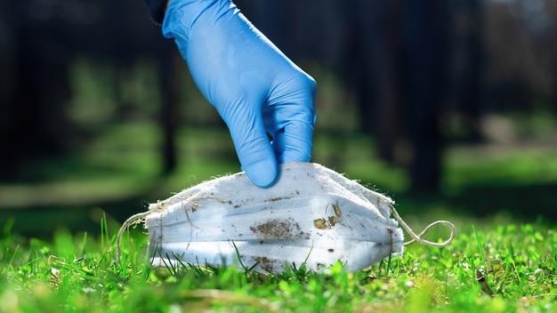 잔디에서 더러운 의료 마스크를 줍는 의료 장갑에 손을 댄다.
