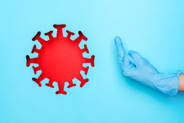 가운데 손가락과 빨간색 코로나 바이러스를 보여주는 의료 장갑에 손을