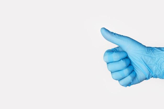 白い背景の上に親指を現して医療用手袋で手。コピースペース