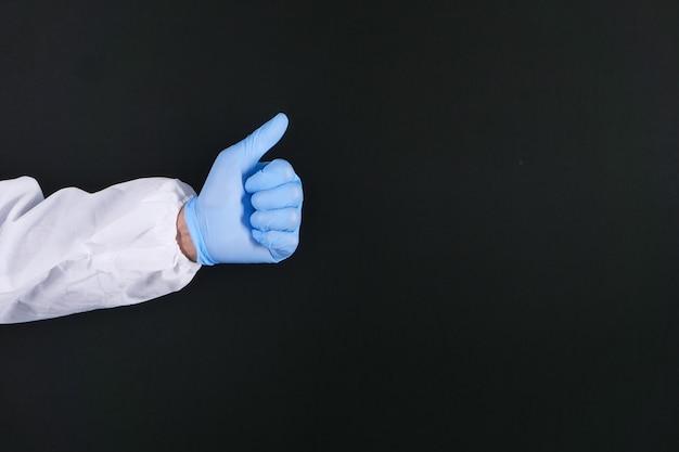 Рука в медицинских перчатках показывает большой палец вверх на черном фоне