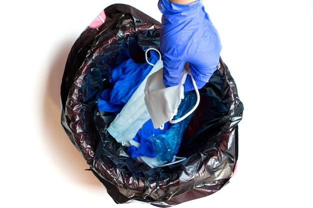Рука в медицинских перчатках выбрасывает использованные защитные маски в мусорное ведро после карантина.