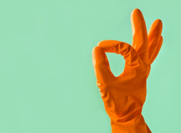 オレンジ色のゴム手袋で手は青い背景に大丈夫親指記号を示しています