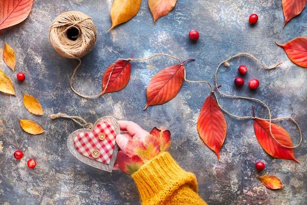 Рука в оранжевом свитере держит деревянное сердце. натуральные осенние украшения, яркие красные, желтые дубовые листья. концепция благотворительной кампании.