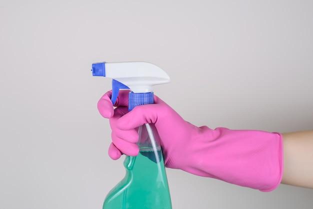 고립 된 파란색 액체와 스프레이 병을 사용하여 분홍색 장갑에 손을