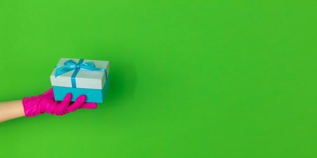 コピースペースで緑のスタジオの背景に分離されたギフトを保持しているピンクの保護手袋を手に入れます。身振りで示す、保持する、物事を提示する。あなたの広告のための否定的なスペース。見せて、指さします。