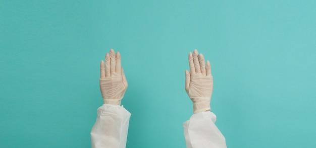 Ppeスーツを着用した医療用手袋の手は、青と緑またはティファニーブルーの背景に人差し指を向けています。