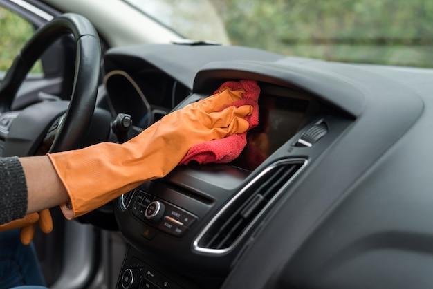 Рука в защитных перчатках, чистящих салон автомобиля