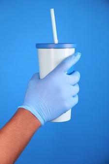 再利用可能なエココーヒーカップを保持している保護手袋を手に