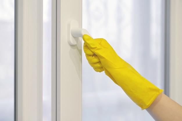 Рука в желтой защитной резиновой перчатке открывает и закрывает пластиковое окно, пвх