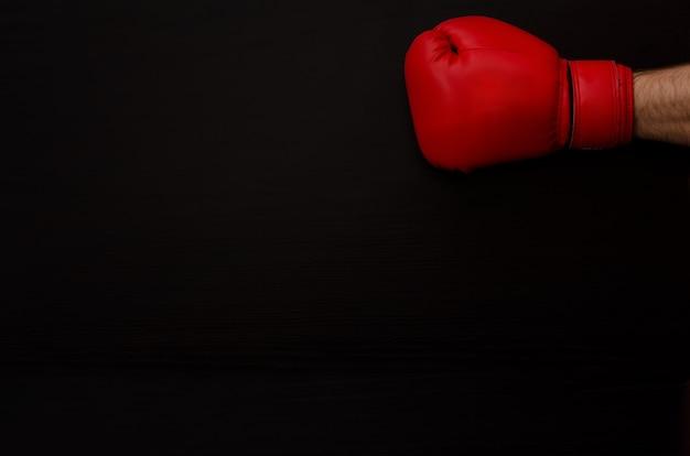 暗闇の中で赤いボクシンググローブを手に