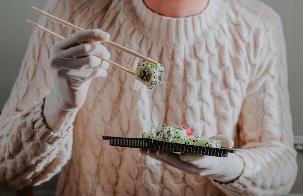 고무 장갑을 끼고 일회용 음식 배달 용기 위에 젓가락으로 초밥을 잡습니다. 스시 메뉴. 일본 요리.