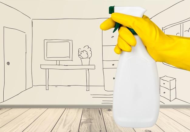 Рука в резиновой перчатке держит бутылку с распылителем на рисованном фоне интерьера