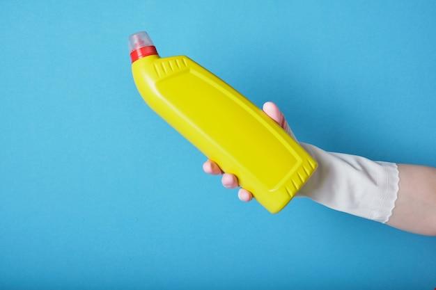 고무 장갑에 손을 파란색 배경에 레이블이없는 화장실 용 세척 젤이있는 노란색 병을 보유하고 있습니다.
