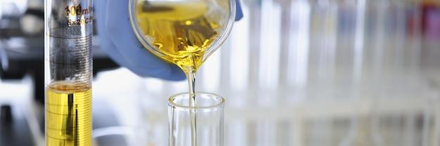 고무장갑을 끼고 화학 실험실이 닫혀 있는 플라스크에 노란색 액체를 붓는다