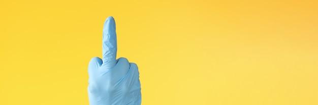 中指のクローズアップを示すゴム手袋を手に。コロナウイルスの概念を停止します
