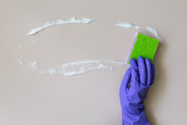 Рука в резиновой перчатке моет очиститель стен.
