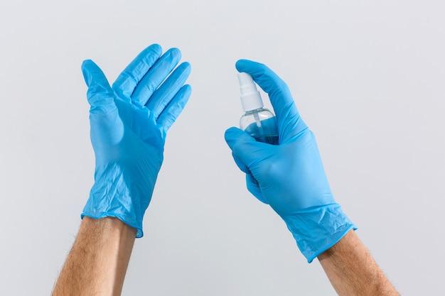 Рука в резиновых хирургических перчатках, держа антисептическое дезинфицирующее средство для рук на фоне. спиртовые дезинфицирующие средства или гель для защиты рук от вирусов короны. антибактериальная жидкость против covid-19