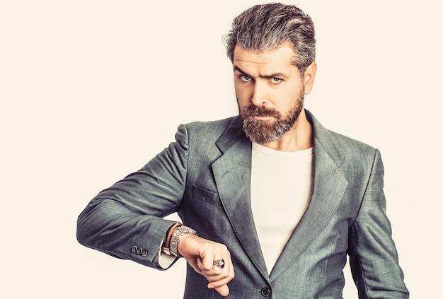ビジネススーツを着た腕時計を手に取ってください。スーツを着たエレガントなハンサムな男。セクシーな男性、残忍なマッチョ、ヒップスター。古典的なスーツを着たハンサムなひげを生やしたビジネスマン。スーツを着た男。男性のあごひげと口ひげ