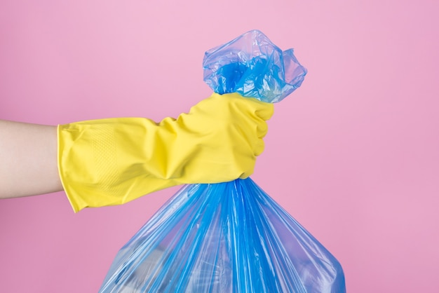 쓰레기 봉투를 들고 노란색 장갑에 손을
