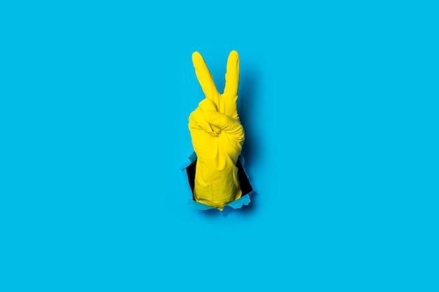 Рука в желтой перчатке показывает два пальца, знак победы и мира ярко-синим цветом