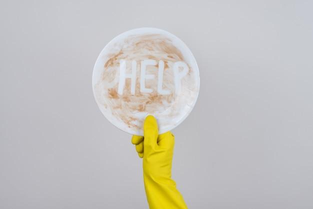 碑文の助けを借りて汚れたプレートを示す黄色のゴム手袋を手に