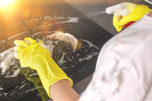 晴れた日に電気ストーブを洗うためにスプレー洗剤を使用して黄色のゴム手袋を手に入れ、キッチンクリーニングのコンセプトの背景写真