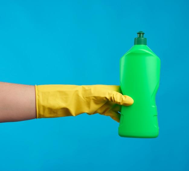 黄色のゴム手袋をはめて緑のプラスチックボトル