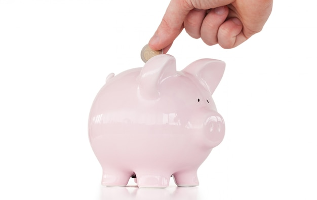 Hand inserting a coin in a pink piggy bank