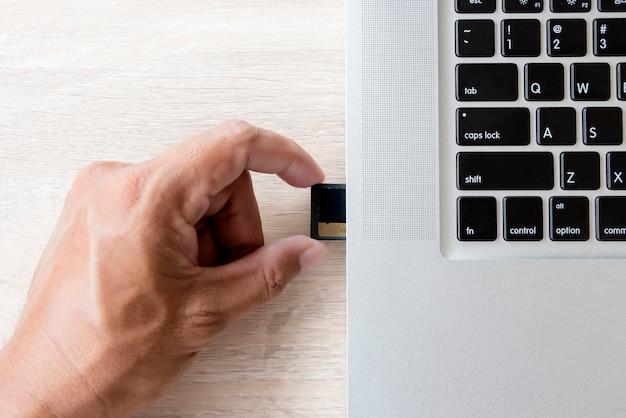 Рука вставляет карту памяти в слот ноутбука