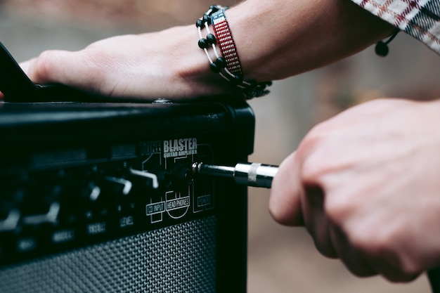 Hand inserts a cord jack into a combo amplifier for electric guitar