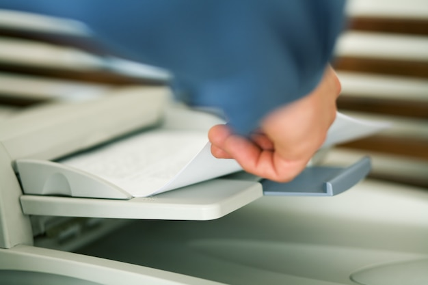 Hand introducing paper inside fax machine
