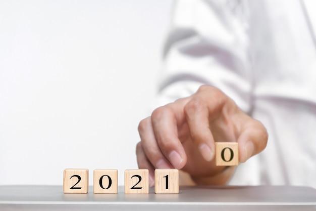 Рука меняет деревянный куб символически меняется с 2020 на 2021 год