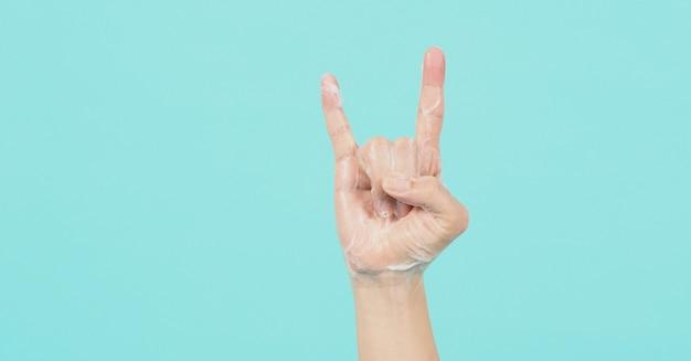손은 악마 뿔 또는 바위 손 기호이며 녹색 민트 또는 tiffany blue background.isolated에 거품 비누 거품이 있습니다.
