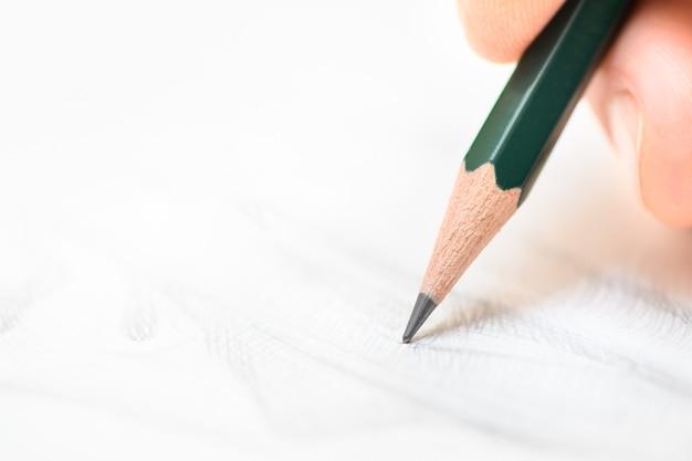 Рука рисует и штрихует на белой бумаге графитным карандашом