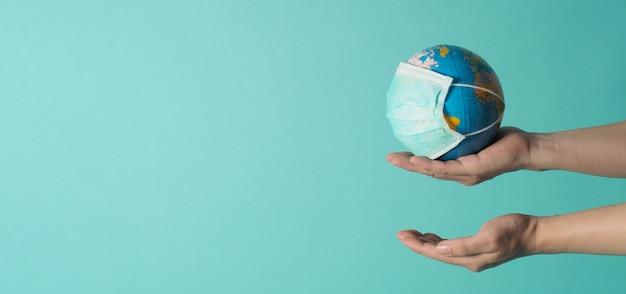 手はミントグリーンまたはティファニーブルーの背景にフェイスマスクで地球儀を保持します。