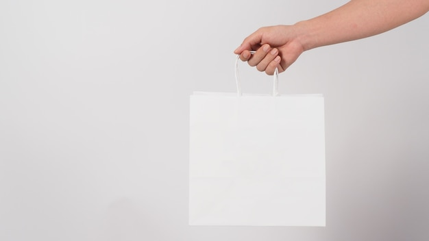 Рука держит белую хозяйственную сумку, изолированную на whitebackground.