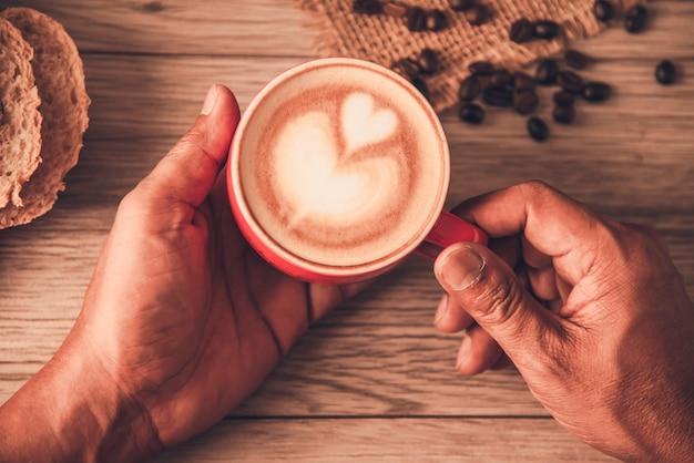 Рука держит красную чашку кофе. концепция натюрморт