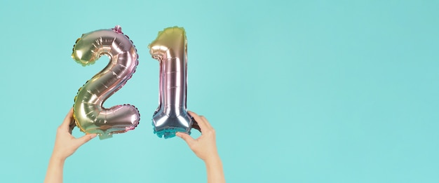 Hand is holding balloon number 21 or twenty one on mint or tiffany blue background.