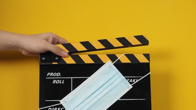 손은 얼굴 마스크가 있는 검정 및 노란색 클래퍼 보드 또는 영화 슬레이트를 들고 있습니다. 노란색 배경의 비디오 제작 및 영화 산업에서 사용합니다.