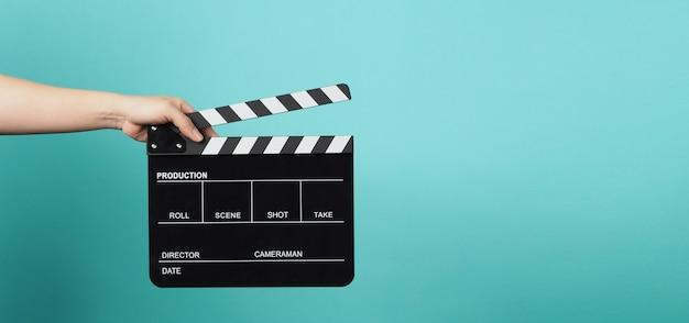 손은 녹색 또는 민트 또는 tiffany blue 배경에 검은색 클래퍼 보드 또는 영화 슬레이트를 들고 있습니다.