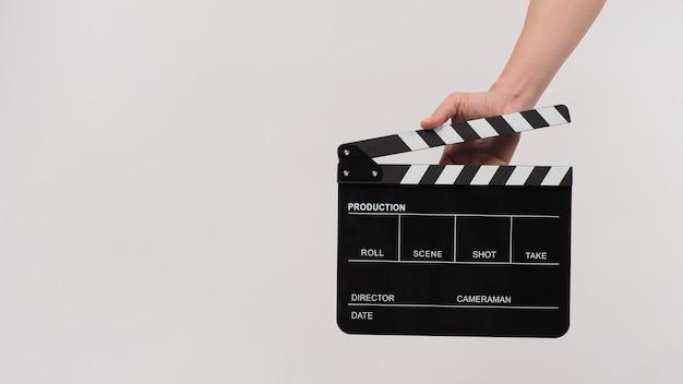 手は白い背景に黒いカチンコまたは映画のスレートを保持しています。
