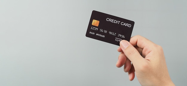 Hand is holding black credit card isolated on grey background.