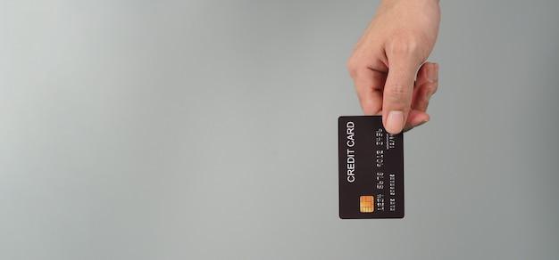 손은 회색 배경에 격리된 검은색 신용 카드를 들고 있습니다.