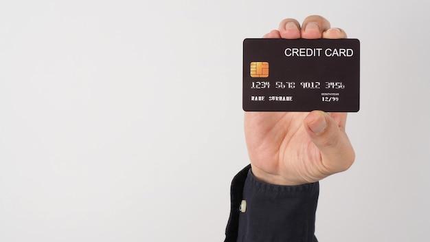 Рука держит черную кредитную карту, изолированную на белом фоне. азиатская рука человека.